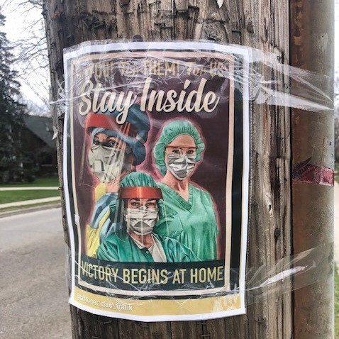 Image of a sign taped to a utility pole telling the viewer to stay inside.